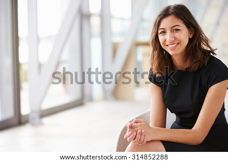 Portrait of young mixed race Asian businesswoman sitting - stock photo