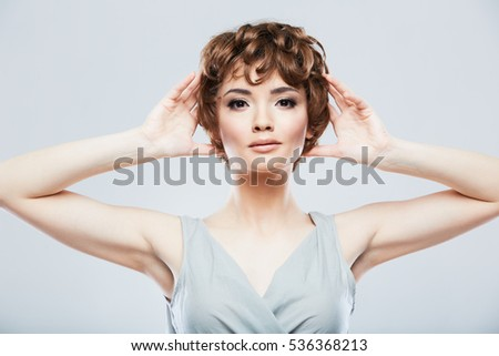 Portrait of young model raised hands. Short hair.