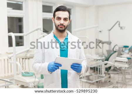 Portrait of young modern doctor dentist with electronic tablet