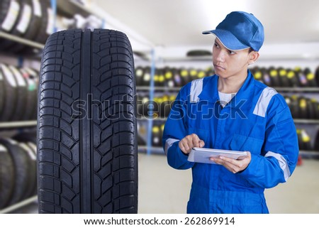 Portrait of young modern technician with a blue uniform using digital tablet to check a tire - stock photo