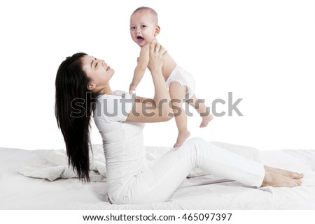Portrait of young mother and cute baby having fun together, isolated on white background