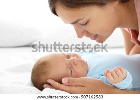 Portrait of young mother and her sleeping baby, close up view