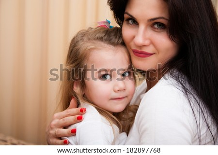 Portrait of young mother and her small daughter.
