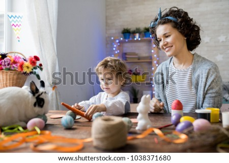 Portrait of young mother and son celebrating Easter at home and playing with cute pet bunny