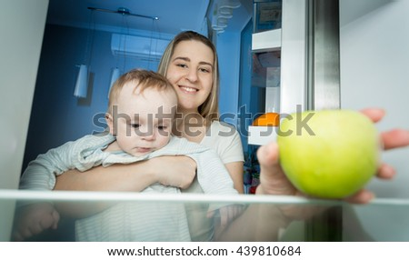 Portrait of young mother holding baby and taking green apple from apple. View from inside of refrigerator