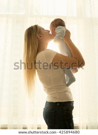 Portrait of young mother holding her little baby at window - stock photo