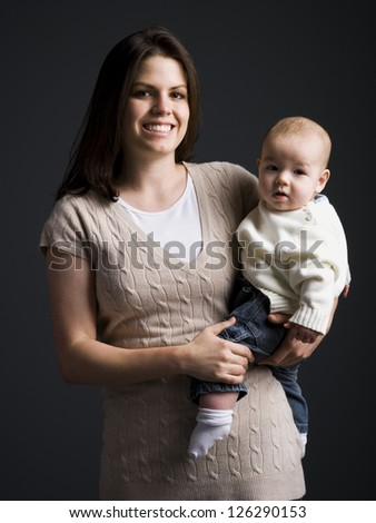 Portrait of young mother holding her little son