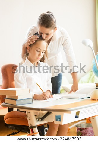 Portrait of young mother hugging and praising daughter while doing homework