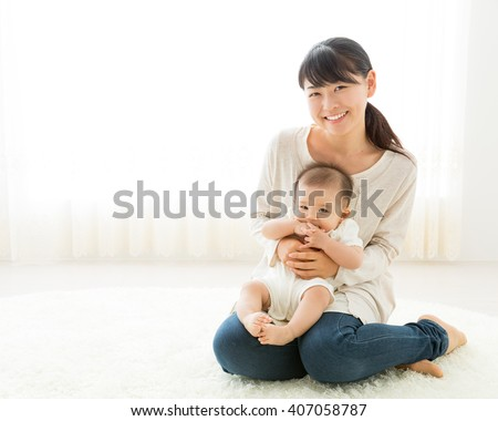 portrait of young mother hugging baby