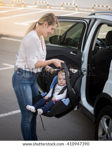 Portrait of young mother installing car child seat with baby - stock photo
