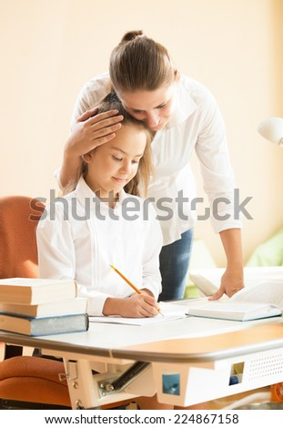 Portrait of young mother praising daughter doing homework at desk