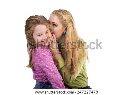 Portrait of young mother whispering secrets in her  adorable daughter 's ear over white background - stock photo