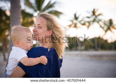 Portrait of young mother with her adorable little boy on the ocean beach. Happy woman hugging a baby and enjoying vacation by the sea. Motherhood. - stock photo