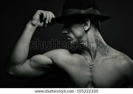 Portrait of young muscular man with hat in studio. Black and white - stock photo