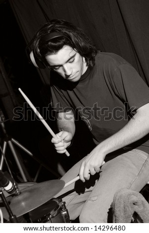 Portrait of young musician playing the drums - stock photo