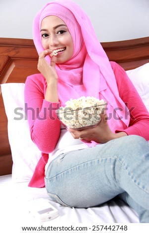 portrait of young muslim woman enjoy eating popcorn on bed - stock photo