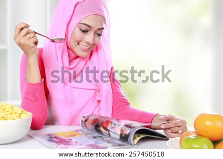 portrait of young muslim woman enjoying a breakfast while reading a magazine - stock photo