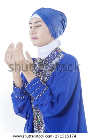 Portrait of young muslim woman in pray gesture, wearing islamic clothes with a blue color in the studio - stock photo
