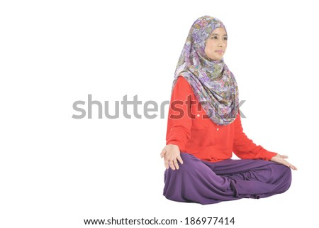 Portrait of young Muslim woman meditating in pose of lotus in isolation - stock photo