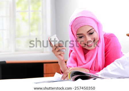 portrait of young muslim woman reading a magazine on bed