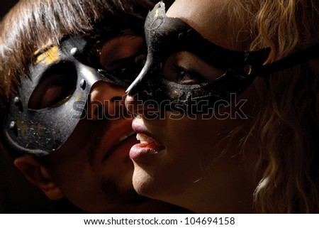 Portrait of young mysterious couple in a Venetian mask - stock photo