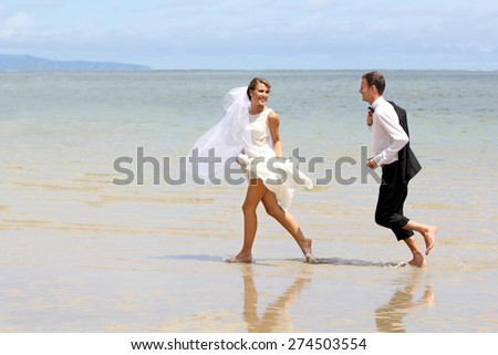 portrait of young newlywed couple playfully at the beach - stock photo