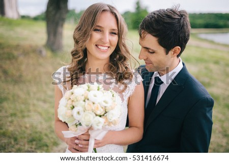portrait of young newlywed couple staring each other lovingly with copy space
