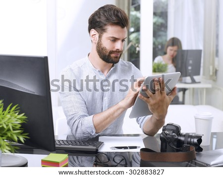Portrait of young newspaper editor sitting at workplace and holding his hands digital tablet while working online.