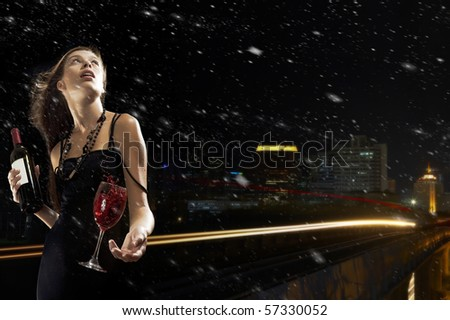 Portrait of young nice woman with glass of wine on black  back