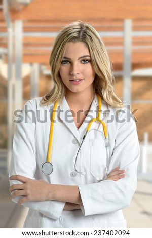Portrait of young nurse or doctor smiling with arms crossed - stock photo