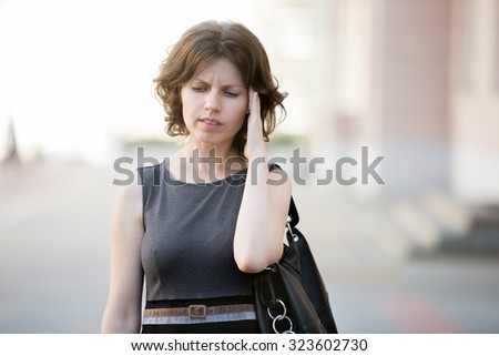 Portrait of young office woman walking on the street in summer, frowning with stressed, confused facial expression, holding her head with hand trying to remember something - stock photo