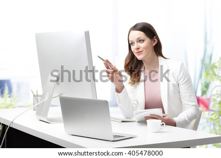 Portrait of young office worker sitting in front of computer at her workstation in an office and working on new presentation. - stock photo
