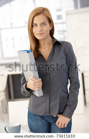 Portrait of young office worker woman standing in office with folder, smiling at camera.? - stock photo