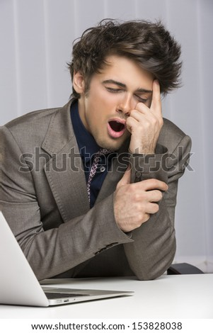 Portrait of young overworked exhausted businessman yawning at his desk at work. - stock photo