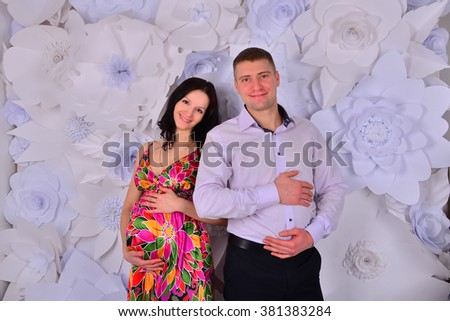 Portrait of young pair pending the kid and showing their their bellie - stock photo