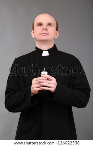 Portrait of young Pastor holding candle in his hand,on gray background - stock photo