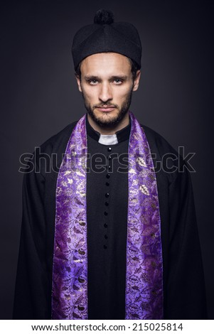 Portrait of young pastor. Studio portrait on black background   - stock photo