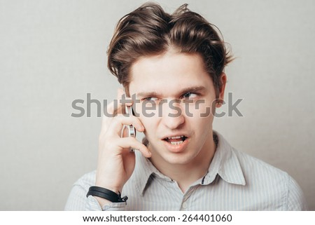 Portrait of young pensive businessman talking on cell phone - stock photo