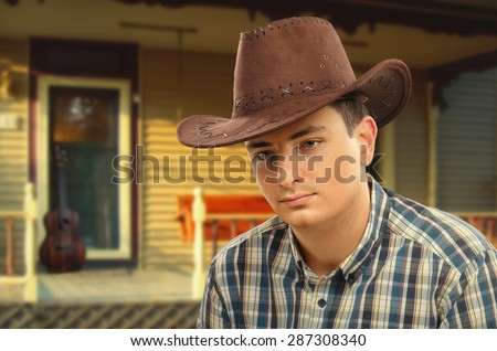 Portrait of young pensive man wearing brown cowboy hat and plaid shirt. In the background is entrance country house. Wooden guitar is leaned to front door. Posed portrait photography - stock photo
