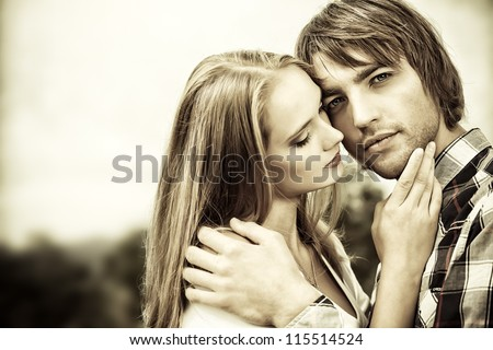 Portrait of young people in love tenderly embracing each other outdoors.