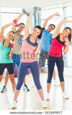 Portrait of young people lifting dumbbell weights with trainer in a bright gym