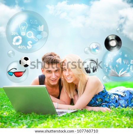 Portrait of young people outdoor resting on green grass and using laptop. Different objects are flying from the screen - stock photo