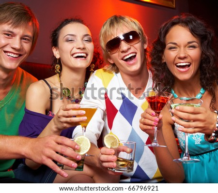Portrait of young people with flutes laughing in the nightclub