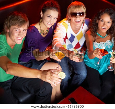 Portrait of young people with flutes looking at you while in the nightclub