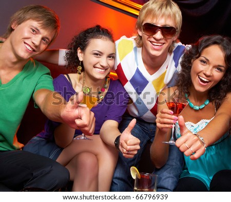Portrait of young people with flutes showing thumbs up in the nightclub - stock photo