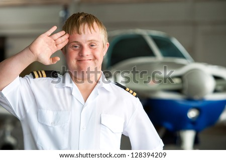 Portrait of young pilot with down syndrome saluting in hangar.