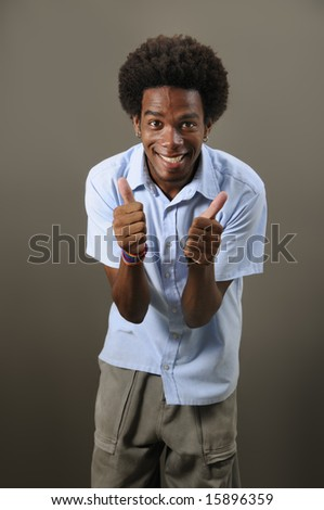 Portrait of young positive african male with thumbs up - stock photo