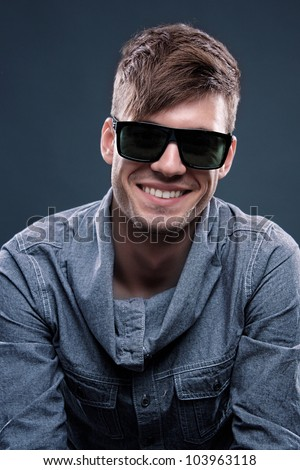 Portrait of  young positive and smiling man in sunglasses on a gray background - stock photo