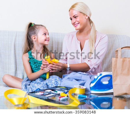 Portrait of young positive mom and child with sewing kit
