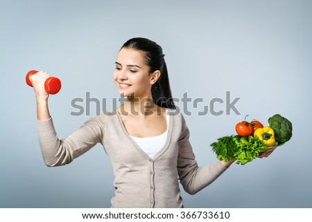 Portrait of young positive woman standing against grey background. Woman holding plate of fresh vegetables and dumbbell. Concept for healthy food and sport - stock photo
